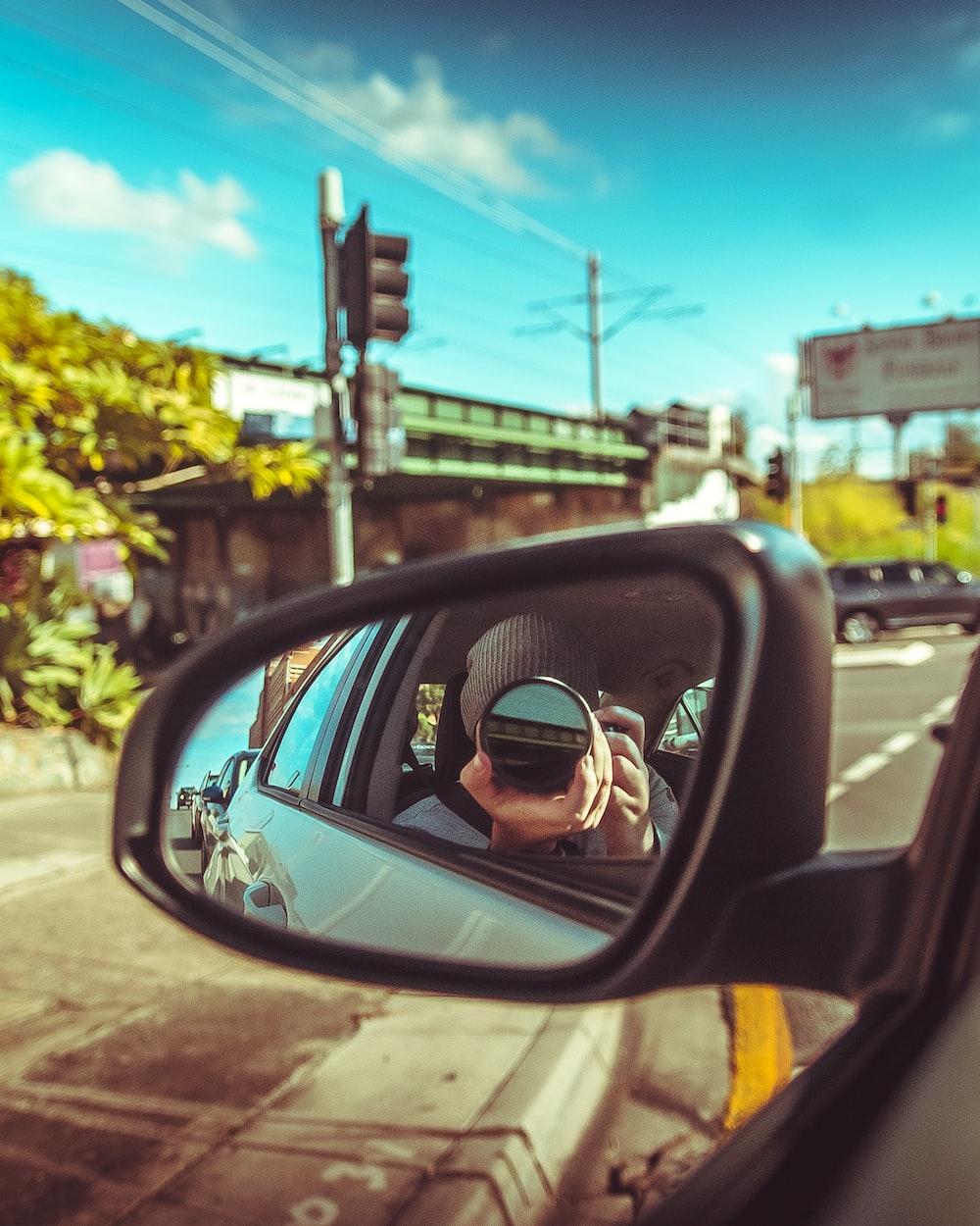 man taking photo of vehicle side mirror