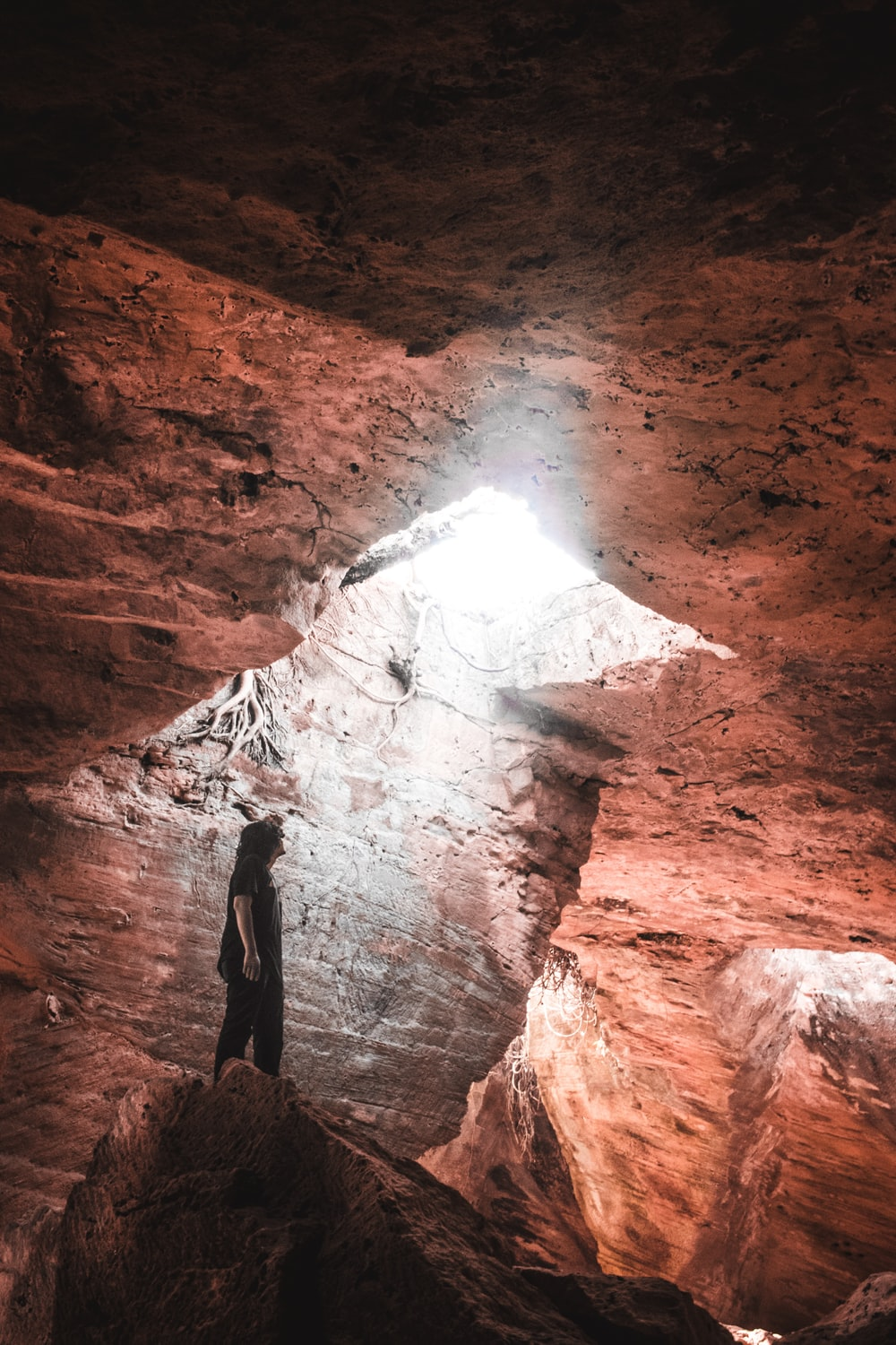 person standing on rock inside the cave