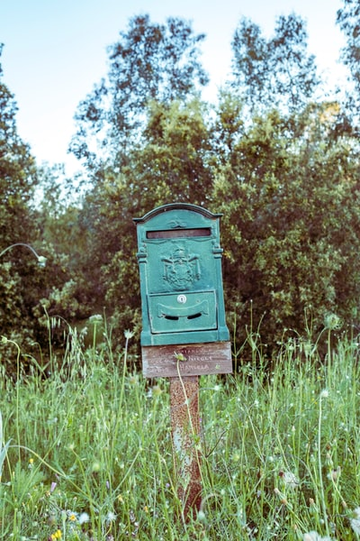 green mailbox on wooden post on grass