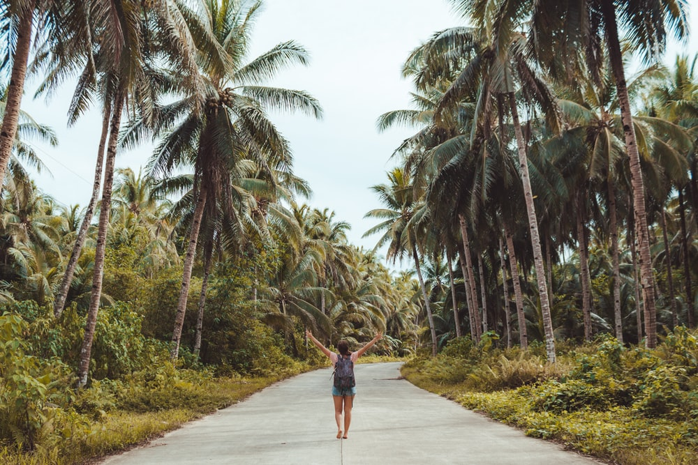 woman walking in the middle of the road raising both her arms surrounded by grass and coconut trees