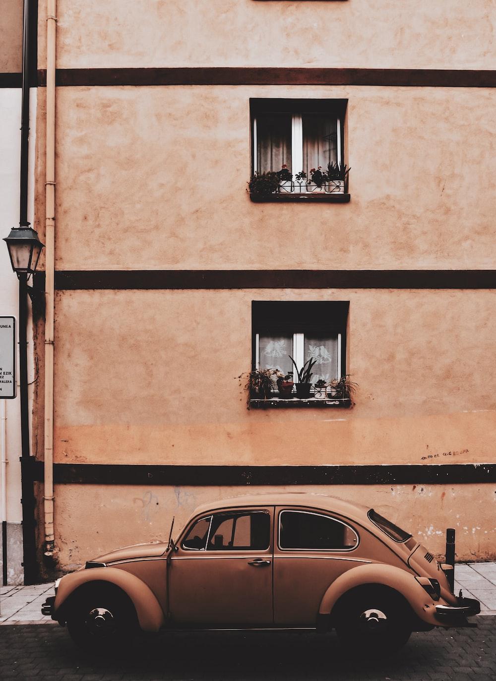 brown Volkswagen Beetle outside hous