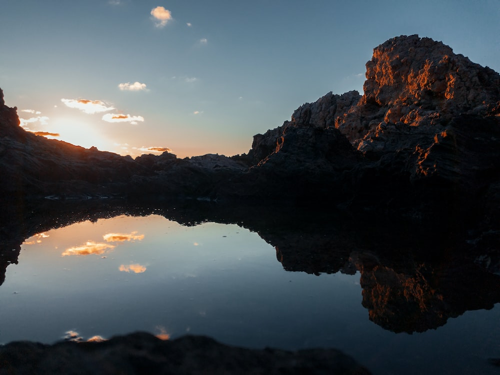 rocky mountain reflecting on water under blue clouds