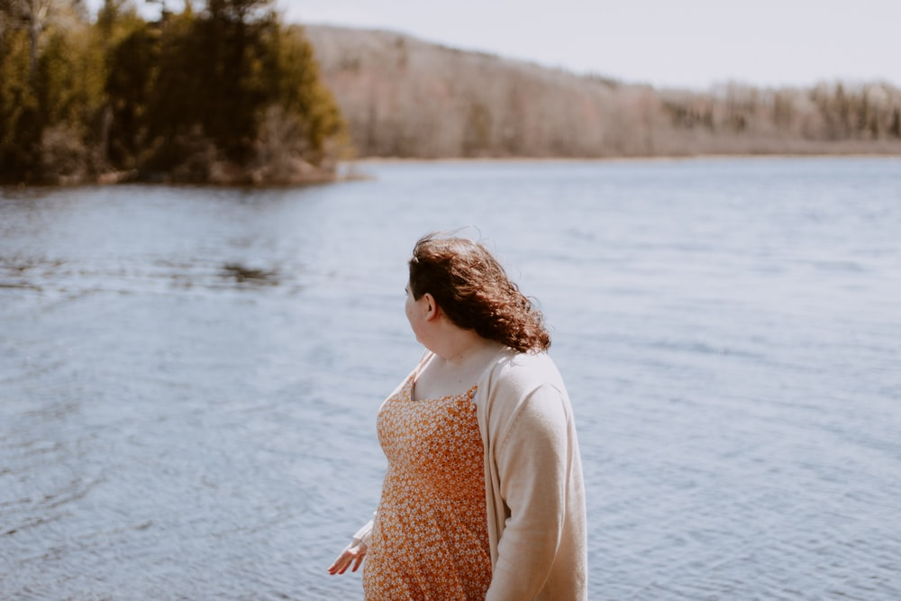 woman wearing gray cardigan looking at body of water