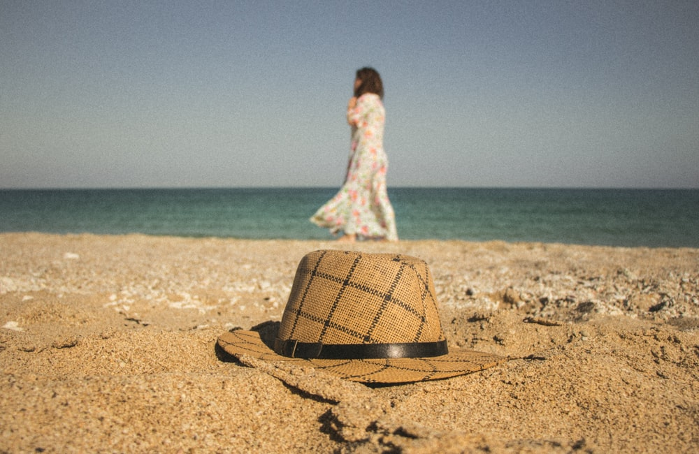 woman walking near seashore and brown and gray hat on brown sand