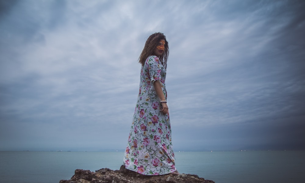 woman standing on brown rock glancing her right side