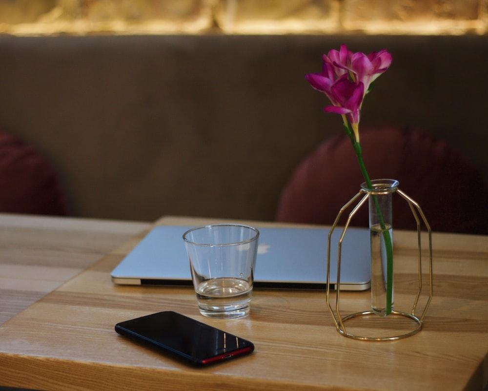 clear shot glass beside black smartphone