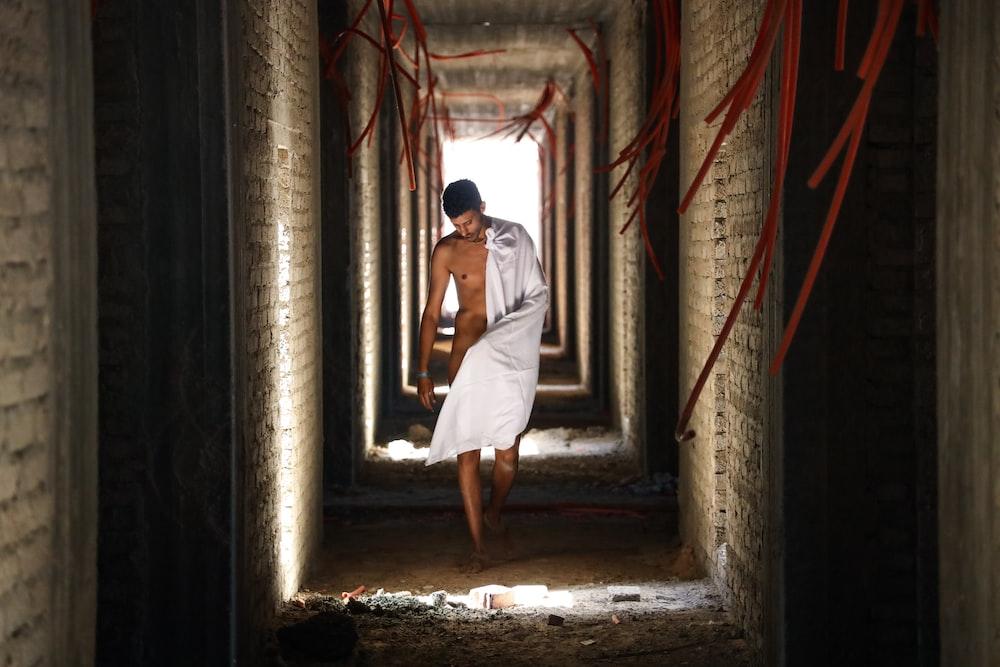 man with white towel walking on hallway