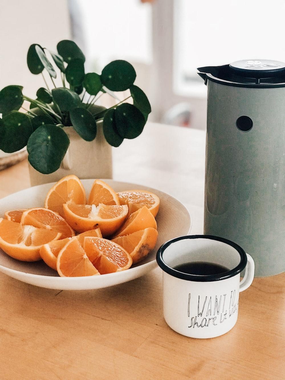 sliced citrus fruit in white bowl beside white mug