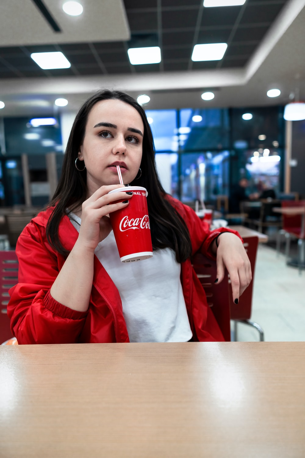 woman sitting while drinking coca-cola