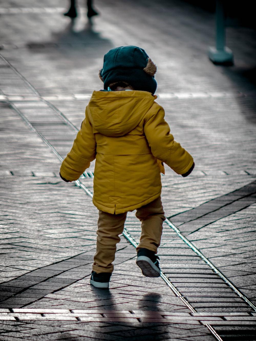 toddler wearing yellow jacket on gray concrete floor