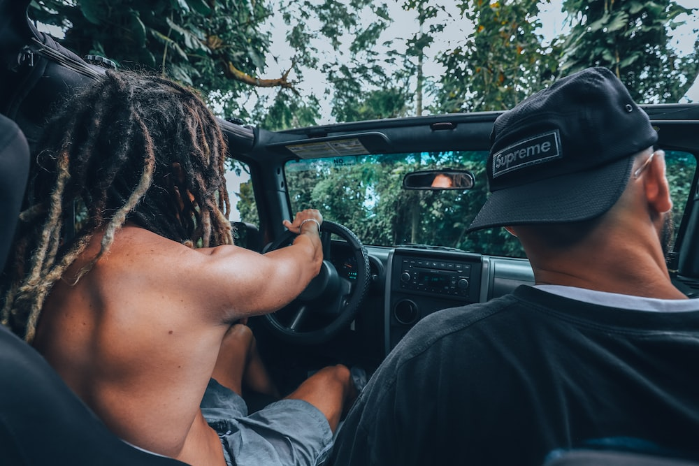 two men riding in vehicle