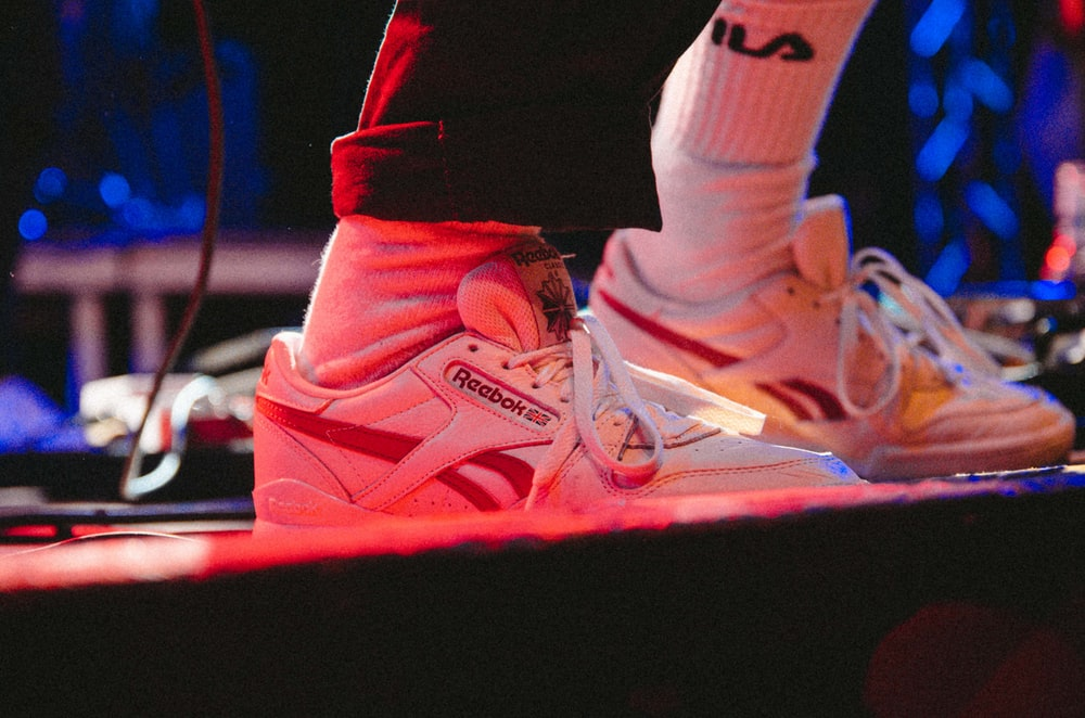 person wearing pair of white Reebok high-top shoes