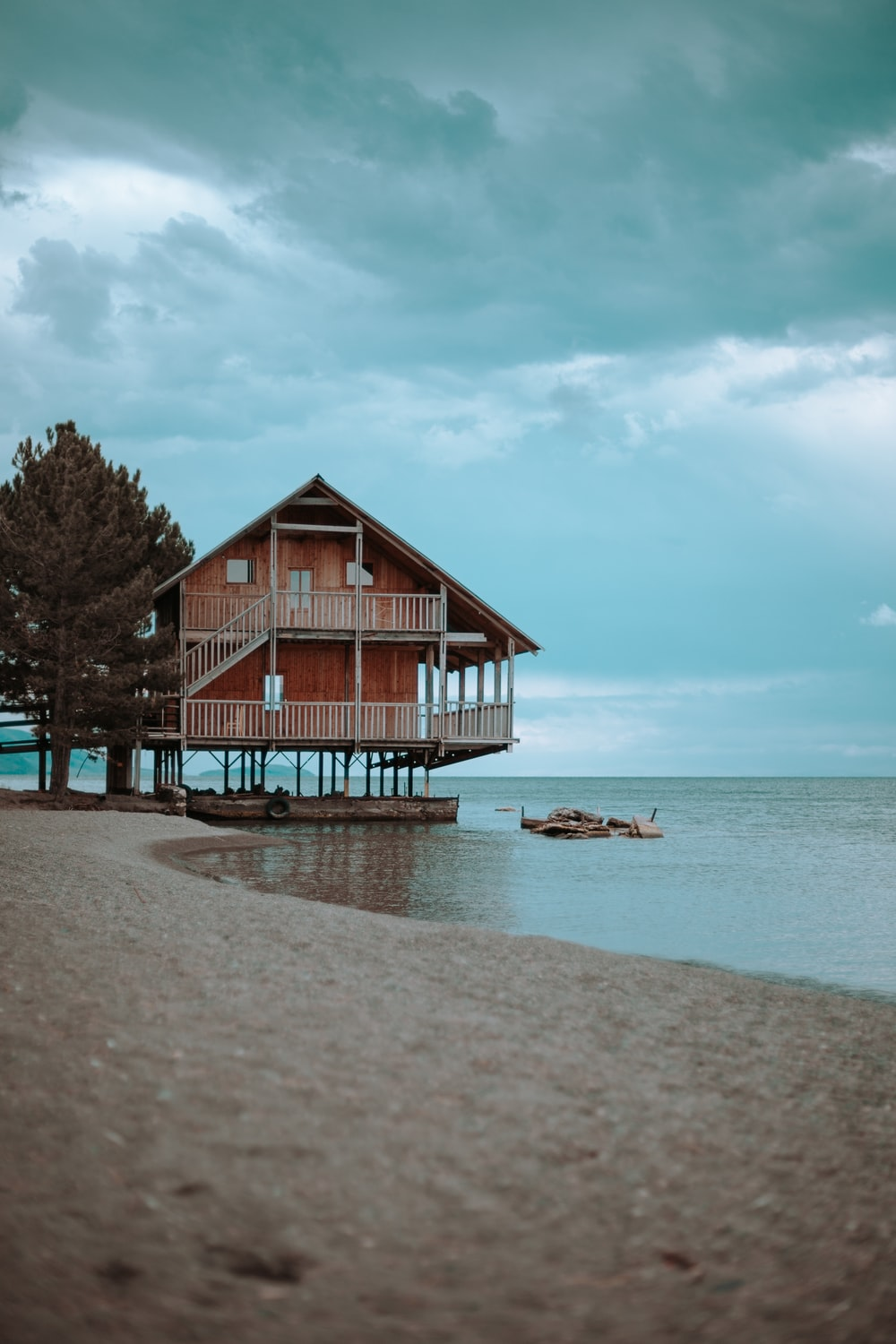 brown wooden 2-story house near body of water