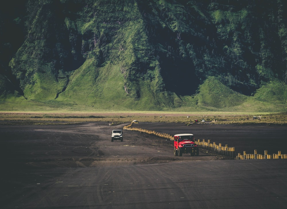 SUVs on dirt road in front of mountain