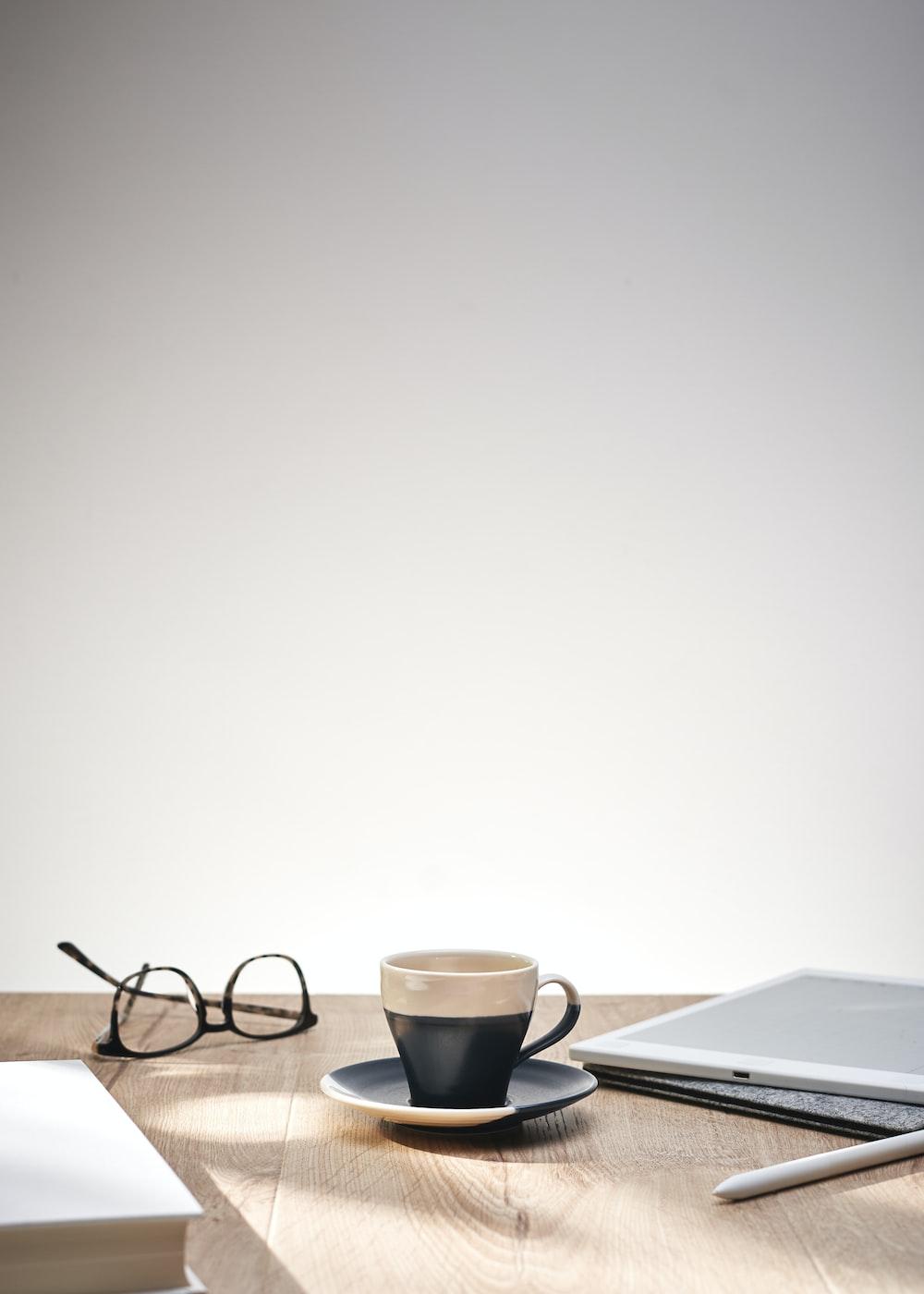 cup on saucer near framed eyeglasses