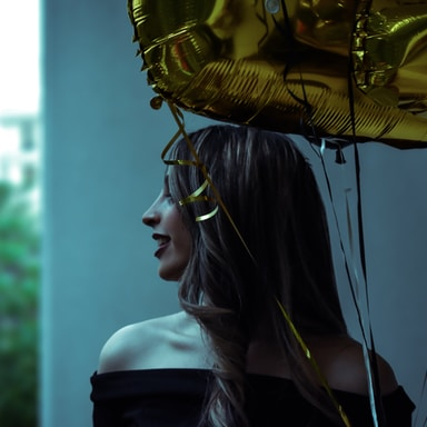 woman in black off-shoulder top holding gold balloon