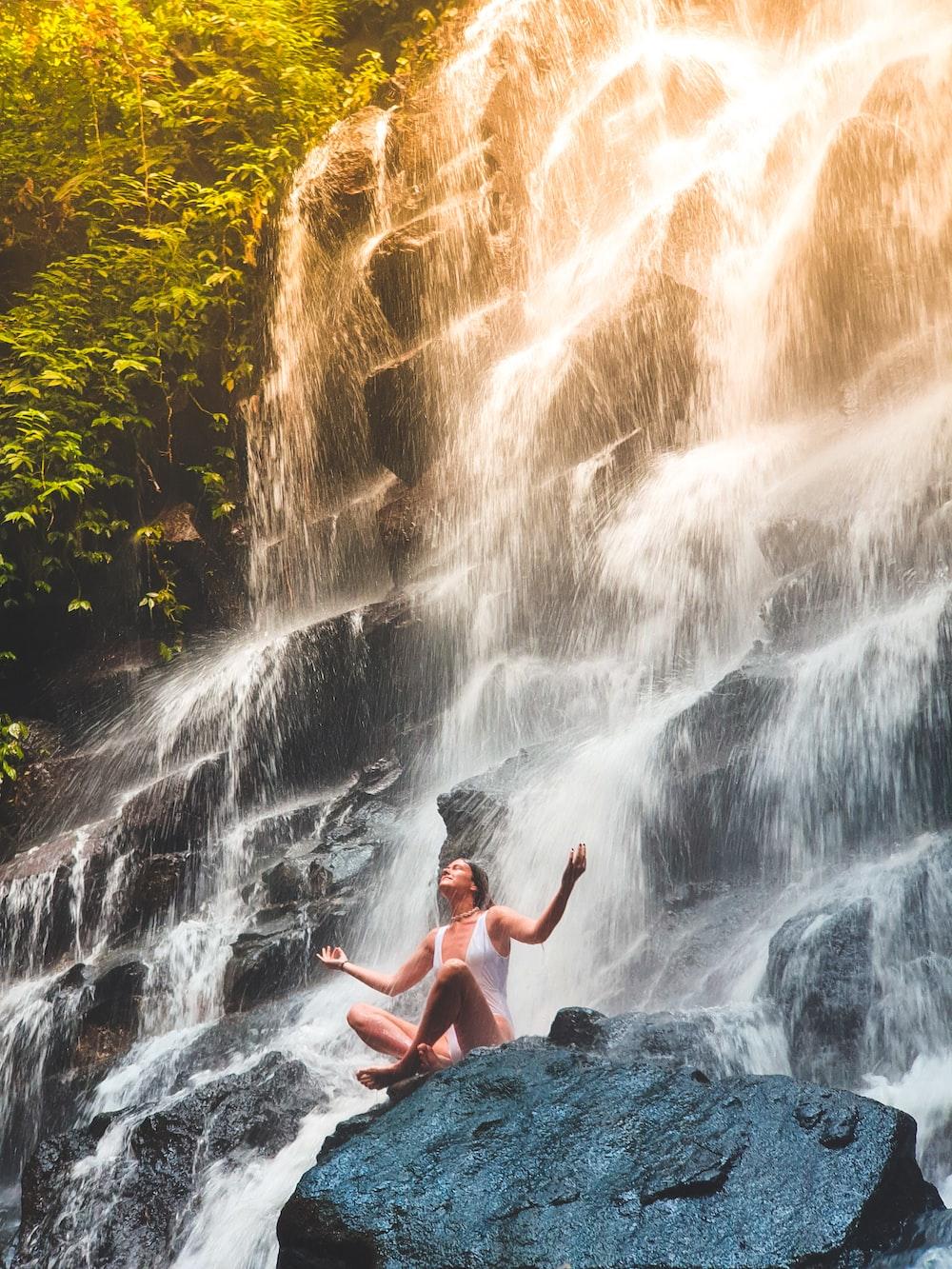 woman in white monokini sitting on rock
