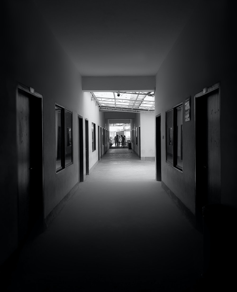 grayscale photography of pathway between rooms