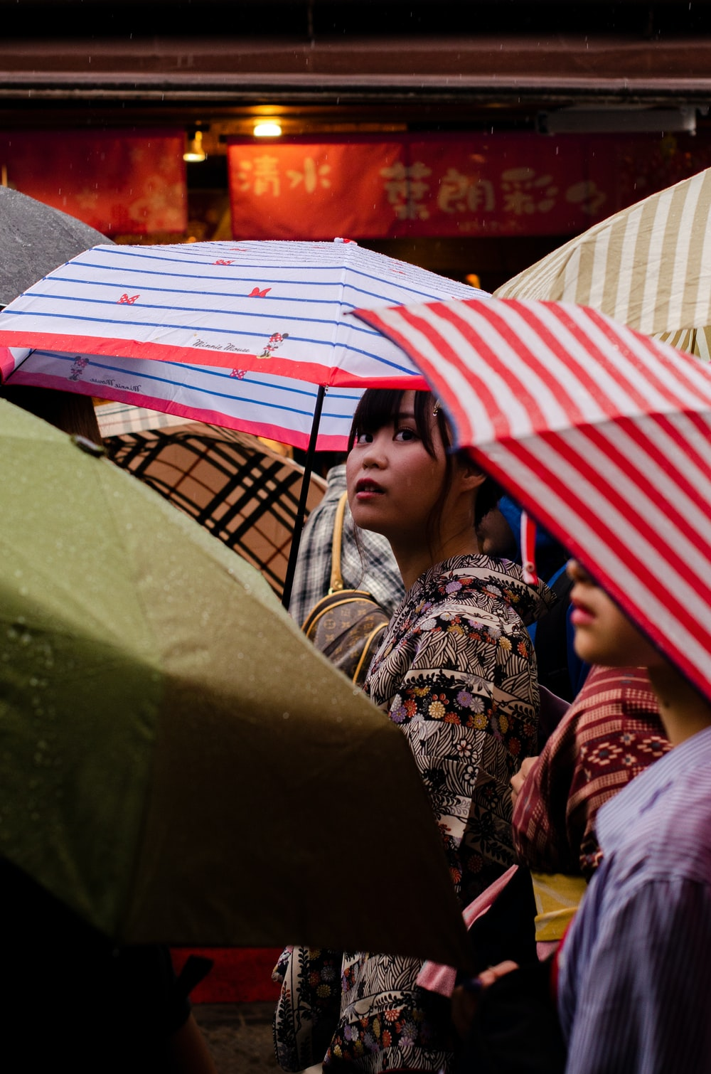 women using a red umbrella during daytime