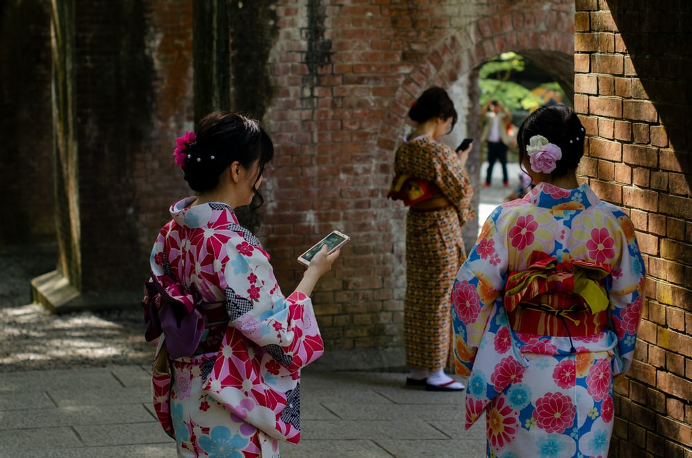 three women wearing kimono dresses during daytime