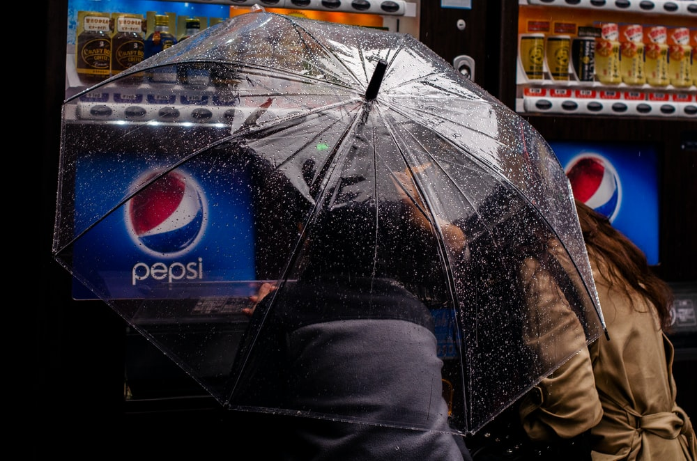 person under clear plastic umbrella near Pepsi vending machine