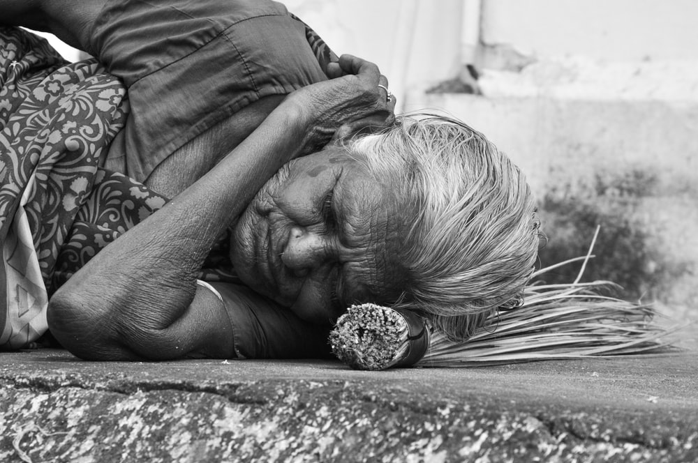 women sleeping on a concrete surface grey-scale photography