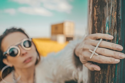 selective focus photography of woman wearing gold-colored cross ring