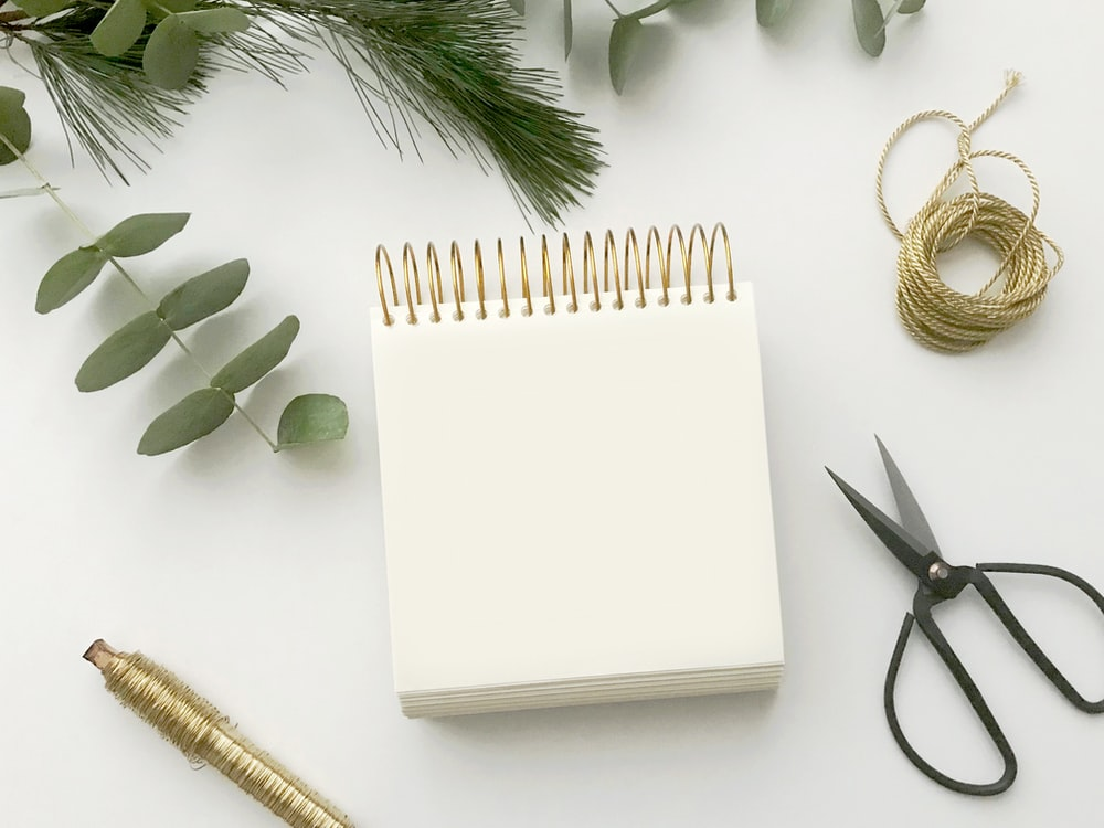 white spiral notepad between pen and scissors