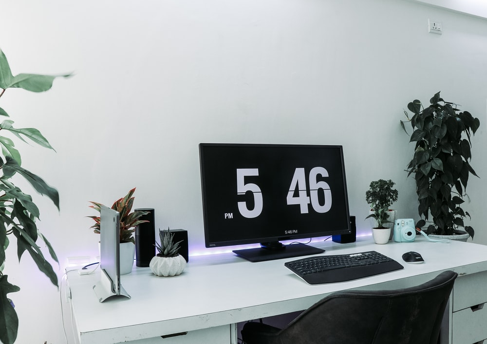 turned on flat screen monitor displaying 5:46