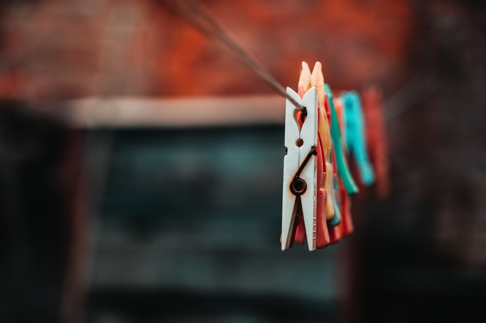 selective focus photography of clothespins on rope