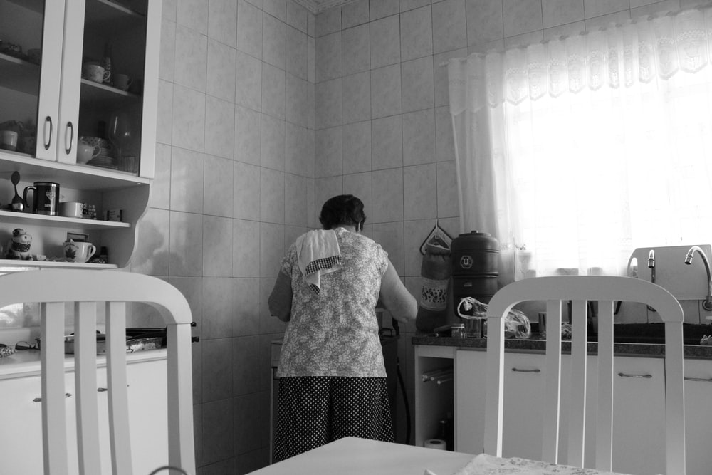 grayscale photography of woman in kitchen