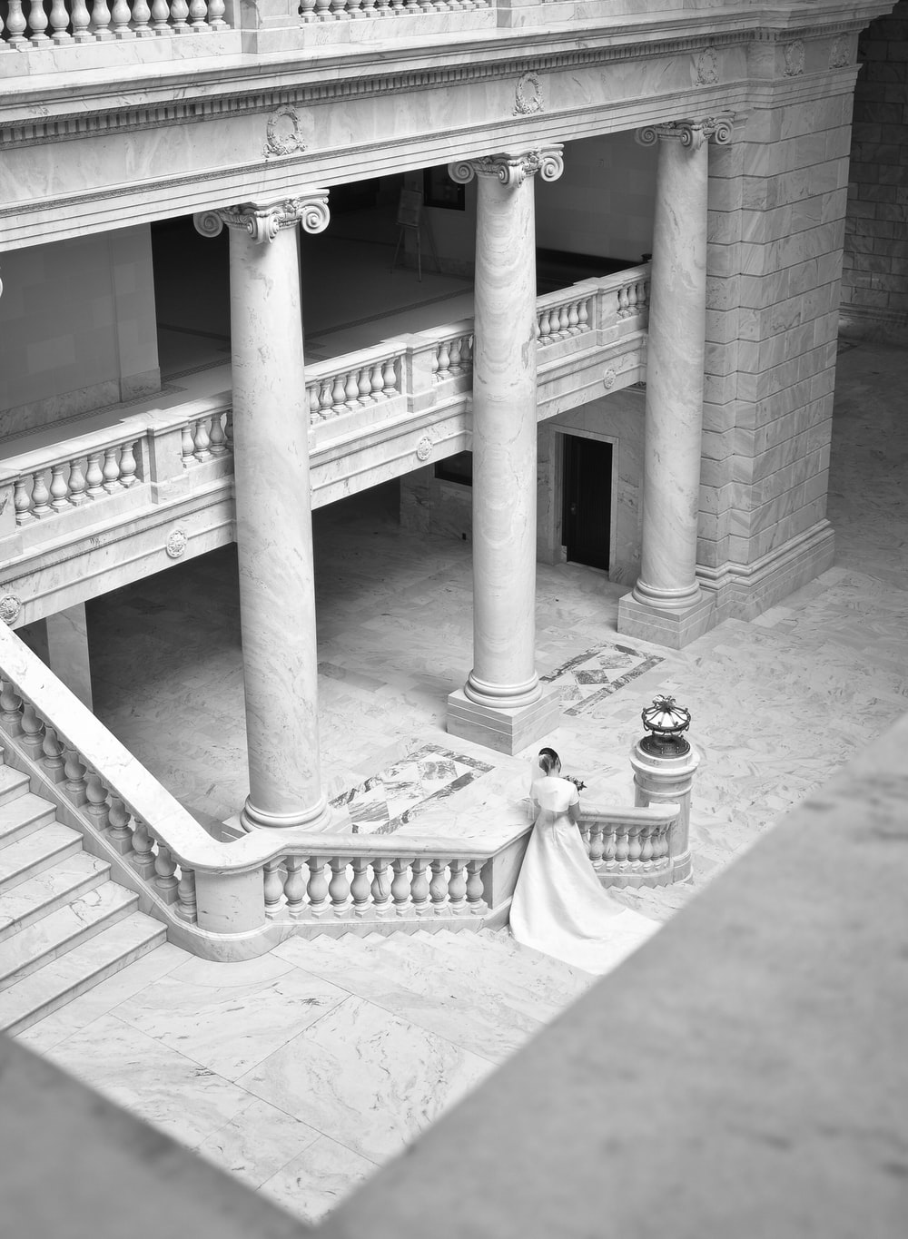 grayscale photography of woman near stairs