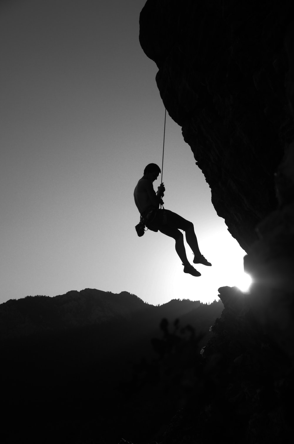 man hanging on cliff