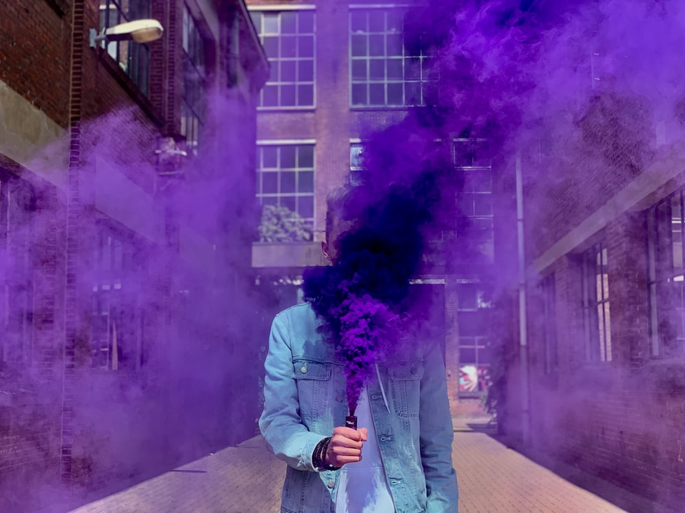 person in blue denim jacket putting smoke bomb near face