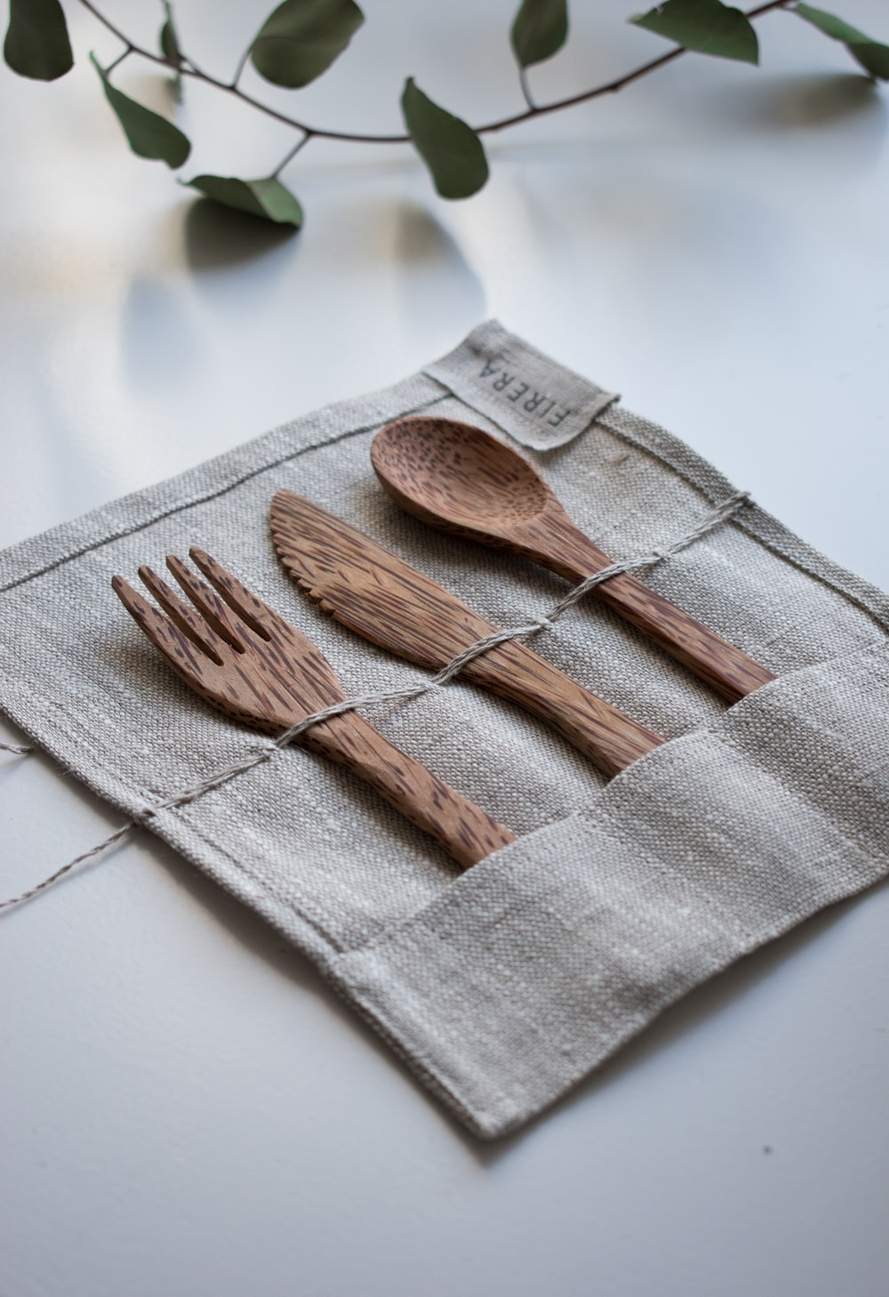 brown wooden fork, spoon, and knife on textile