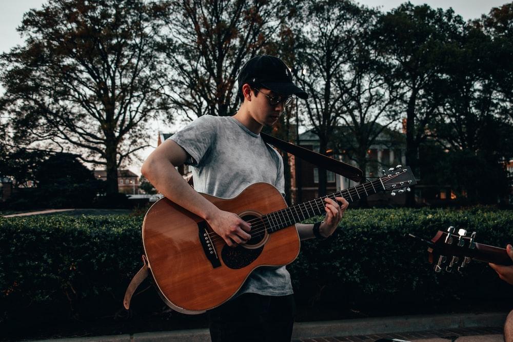 man carrying guitar while playing