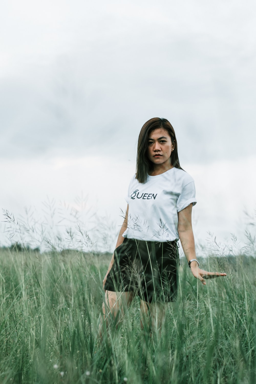 woman in white shirt standing on grass field during daytime
