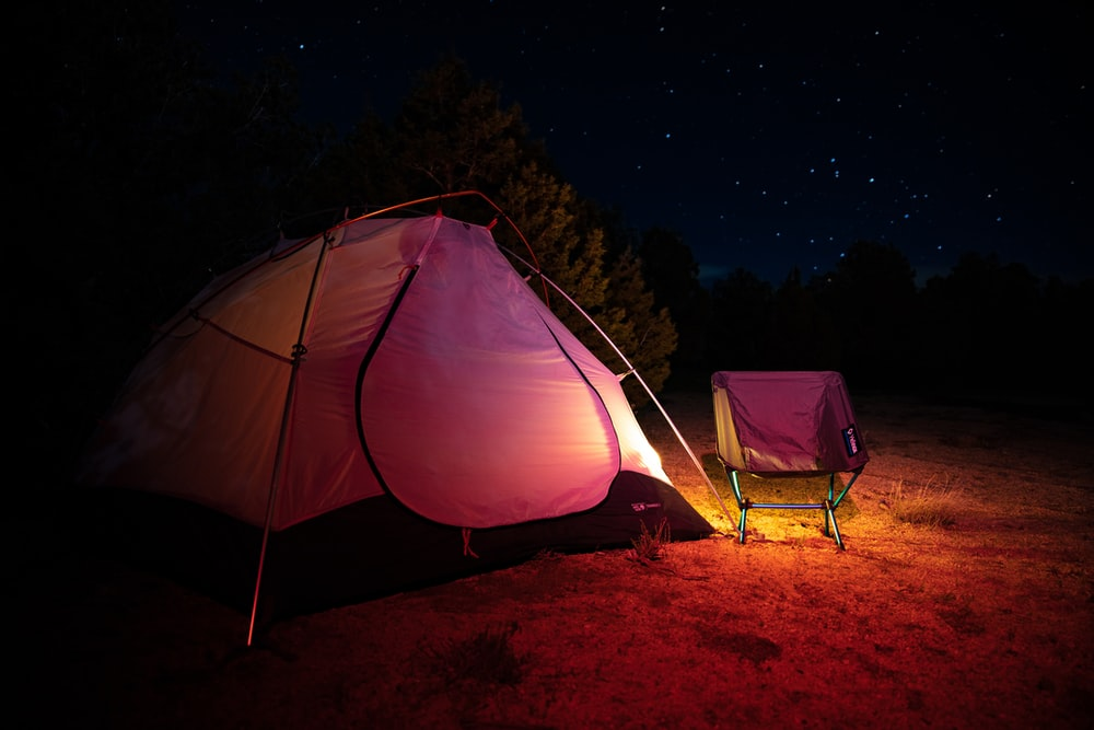 light coming from pink and orange tent near pink camping chair