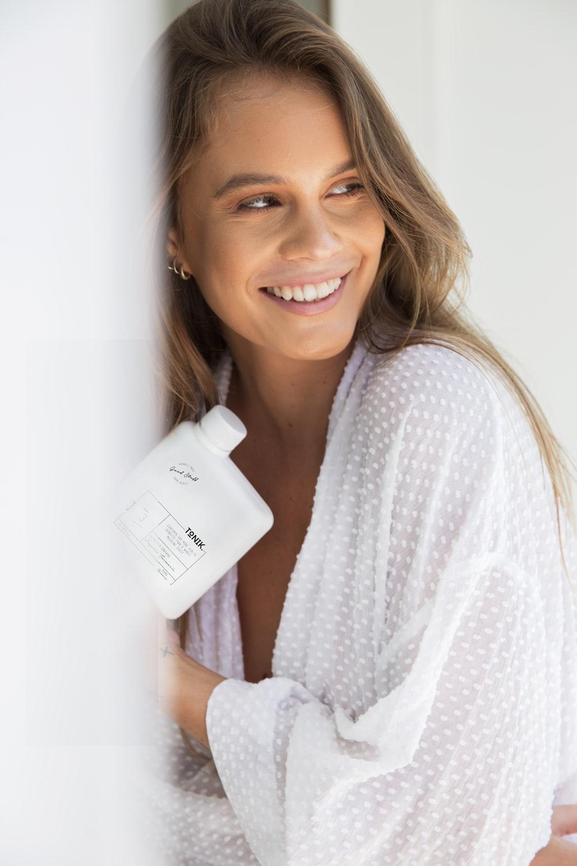 smiling woman wearing white robe