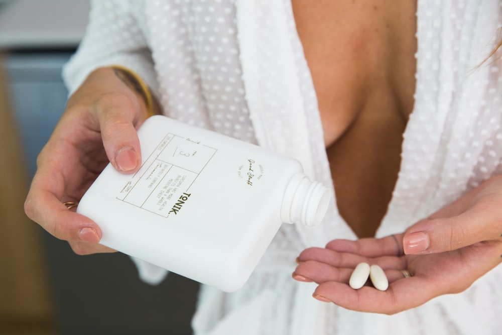 woman holding white medication pill