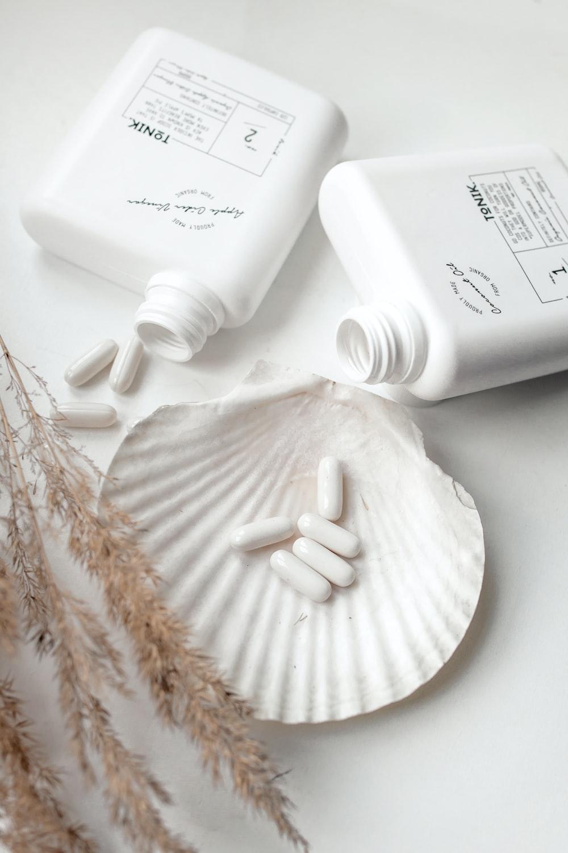 medication pills on white shell beside plastic bottles