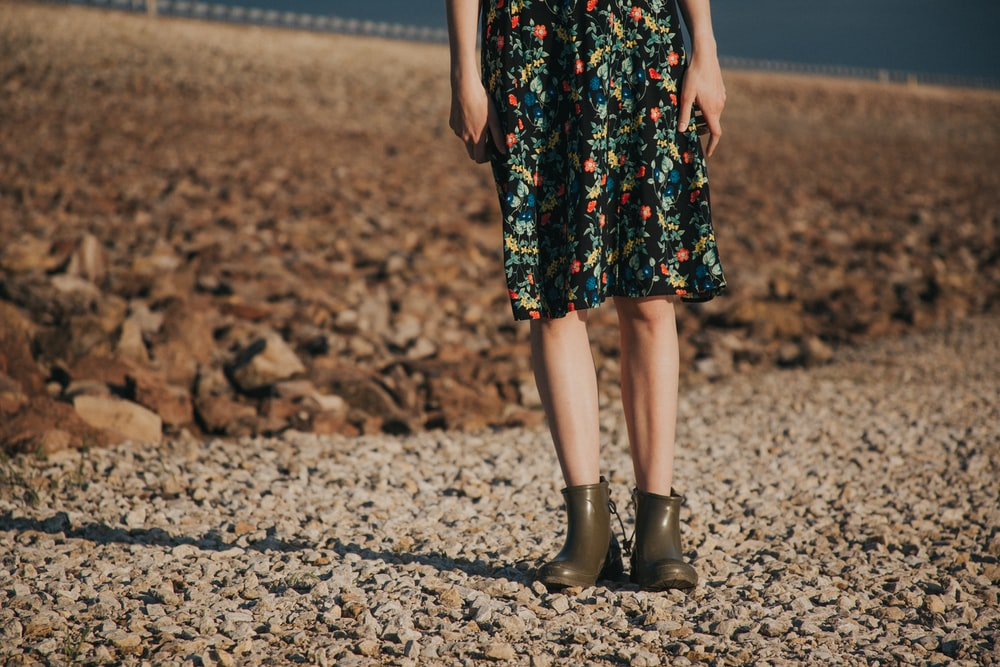 woman standing on gravel wearing floral dress