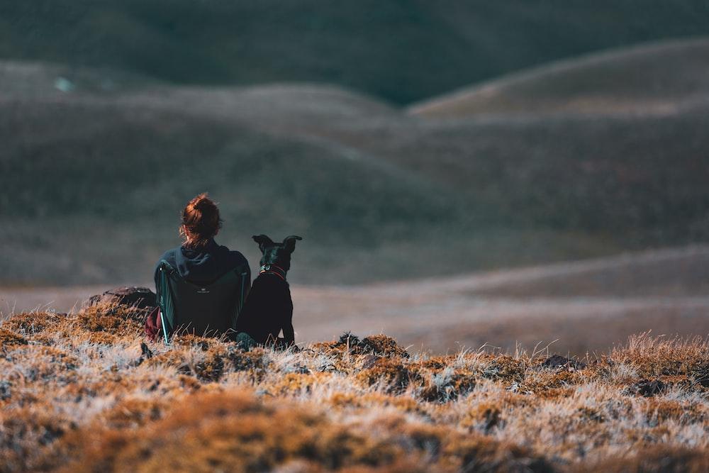 woman sitting beside black dog