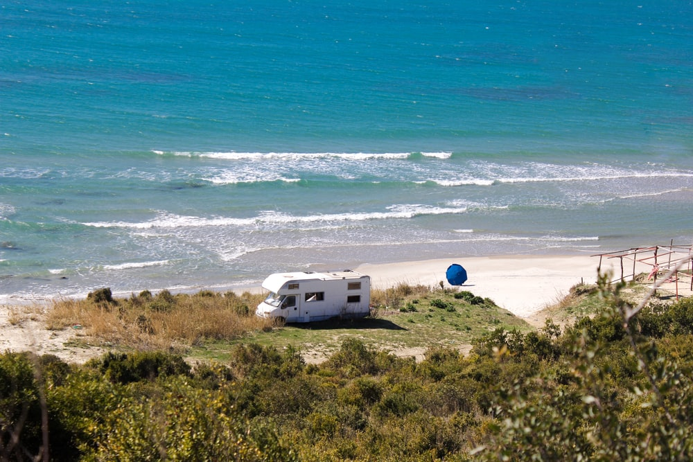 white RV near the ocean