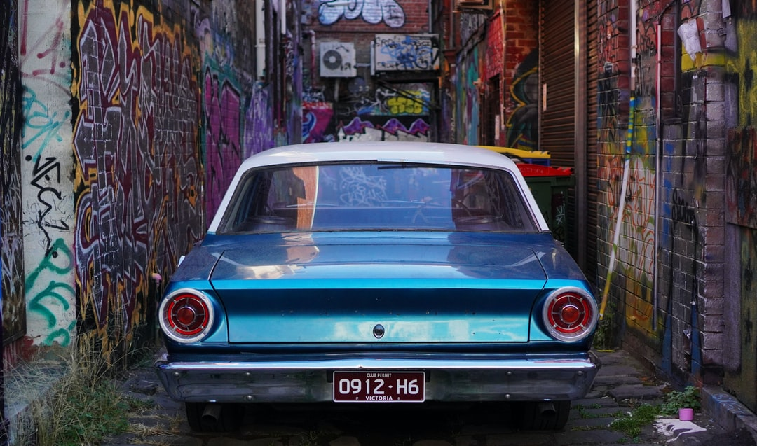 A photo of a vintage car parked in a graffiti covered alley.