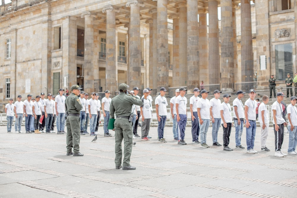 people standing and forming straight line near another two soldier men