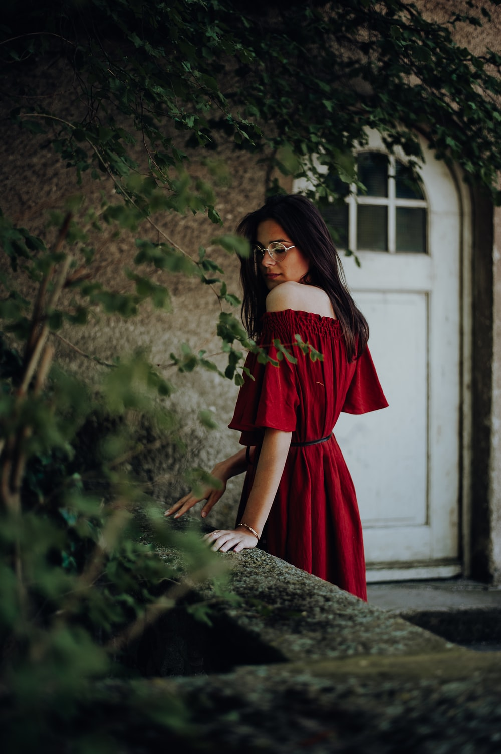 woman in red off-shoulder short-sleeved dress near brown concrete building