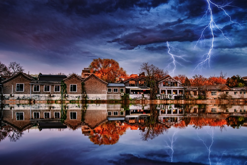 reflection of houses on body of water under dramatic clouds