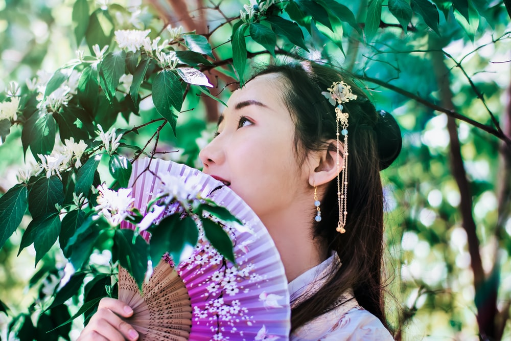 woman holding fan under tree