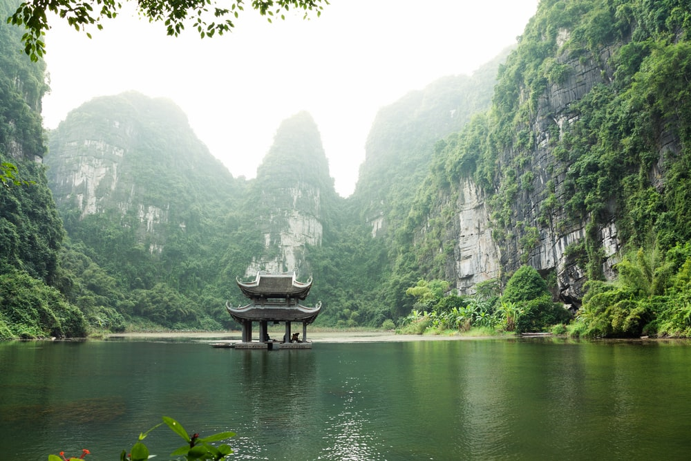 pagoda surrounded by body of water and mountains